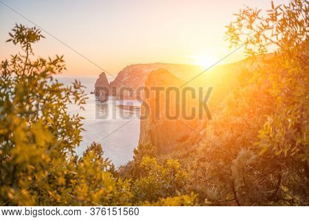 Autumn Sea Landscape With Warm Sunset Light Over Rocky Coastline. Calm Sea On A Background Of Rocky