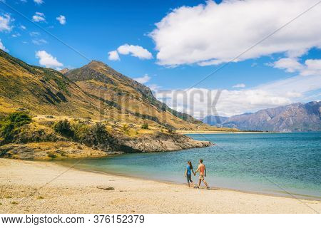 New Zealand travel people tourists visiting Otago region walking on shore of lake Hawea nature landscape. Man and woman happy at beach Near Wanaka. Young tramping hikers adventure lifestyle.