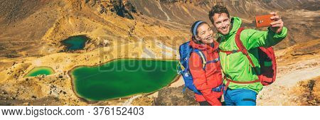 New Zealand Tongariro Alpine Crossing Hiking tourists couple selfie at Emerald Lakes. Happy backpackers tramping taking phone photo of themselves at volcanic mountains. Tramping track of New Zealand.