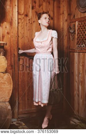 Young, Good-humoured, Red-blonde Woman In Dirndl With Bag At The Entrance Of A Mountain Hut