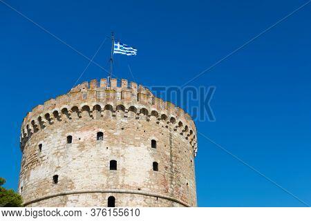The White Tower in Thessaloniki with waving Greek flag, Greece. Greek landmark