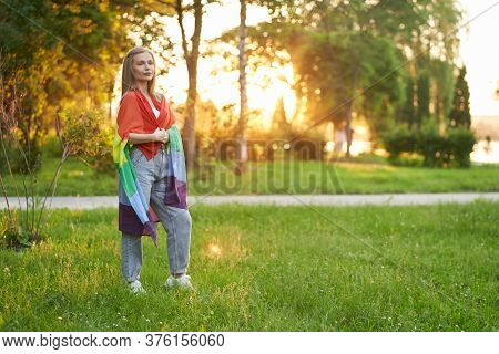Young Caucasian Tolerant Woman Posing In Park, Summer Sunset On Background. Attractive Girl With Str