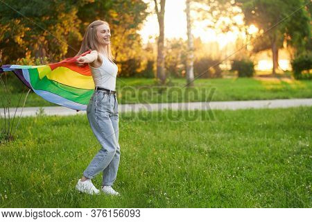 Side View Of Happy Laughing Girl Dacing, Swinging Rainbow Lgbt Flag On Wind Behind Back, Summer Suns