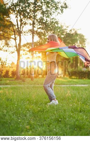 Young Happy Woman Swinging Rainbow Lgbt Flag On Wind Behind Back While Dancing. Side View Of Laughin