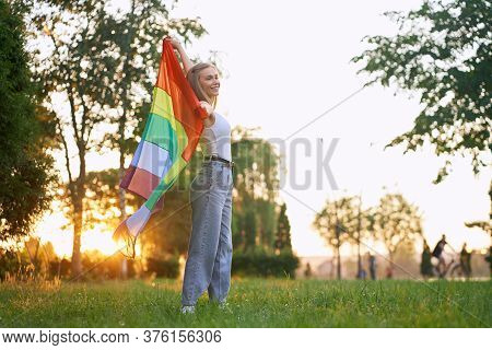 Full Lenght From Below Side View Of Smiling Girl Posing In Park, Enjoying Summer Sunset. Young Prett