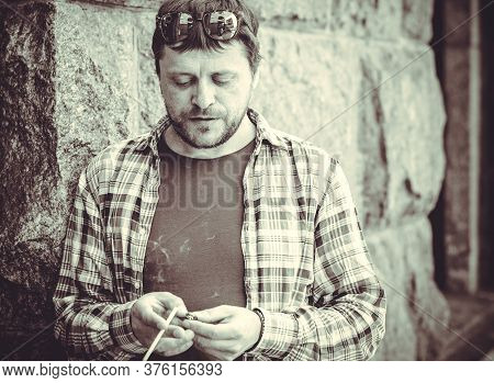 A Man, A Resident Of A Large Metropolis, Leads An Unhealthy Lifestyle, Stands And Smokes Cigarettes