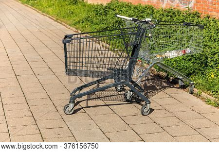 Shopping Trolley In Black On The Street, On The Sidewalk. Sidewalk In The Parking Lot Next To The St