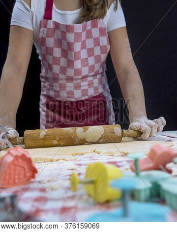 Girl Rolling The Dough With A Rolling Pin On The Table. Baker Background