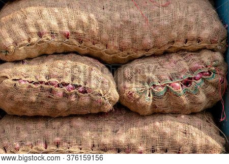 Pile Of Onion Sacks In An Indian Vegetable Market For Selling And Exporting