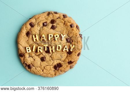 Giant chocolate chip cookie with happy birthday written in gold letters