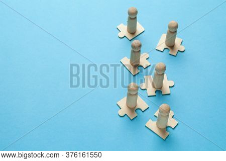 Wooden Figures On Puzzles On Blue Background As A Symbol Of Team Building. Organization Group People