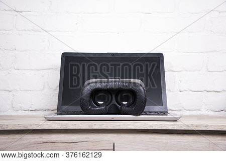 3d Glasses And Laptop On A Wooden Table Against A Brick Wall