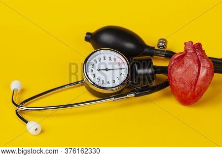 Heart And Mechanical Blood Pressure Monitor On Yellow Background. Measurement And Control Of Blood P