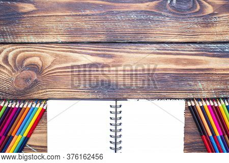 School Supplies Notebook And Color Pencils On A Wooden Table With Space For Text, Top View