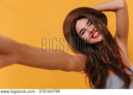 Tanned Lady With Blissful Face Expression Making Selfie And Laughing. Carefree Girl Wearing Hat Taki