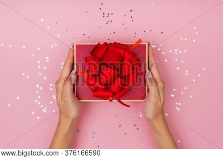 Women Hands Holding A Gift Or Gift Box Decorated With Confetti On A Pink Pastel Table Top View. Flat