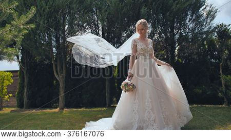 A Young Bride Is Standing In A Park And Her Veil Is Slowly Falling Her Veil Is Slowly Falling