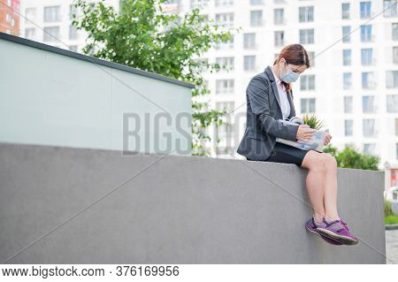 Depressed Woman In Medical Mask Sits On Parapet Outdoors With A Box Of Personal Items From The Deskt