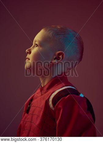 Portrait Of Boy Kid Racer In Racing Suit, Standing In Neon Light. Kart Racing School Poster. Competi