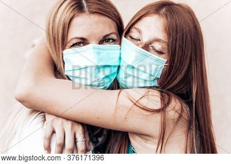 Close-up Portrait Of Mom And Daughter Hugging Wearing A Medical Mask. Corona Virus Family Concept