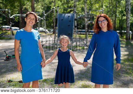 Homosexual Lesbian Couple Hold Daughters Hands. A Girl Walks With Two Mothers In The Park. Two Marri