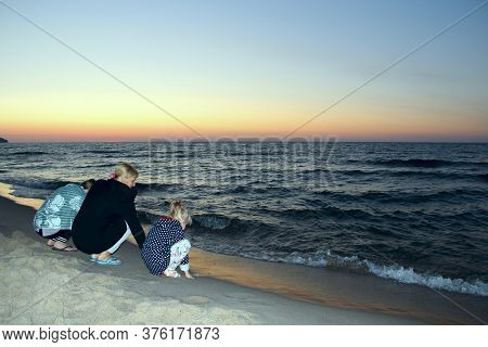 Mother With Children Enjoy The Evening Baltic Sea And Sunset. Family Enjoying Sunset And Rest By Sea