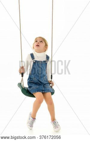 Cute Happy Girl Sitting On Rope Swing And Looking Up, Lovely Blonde Girl Wearing White Sweatshirt An