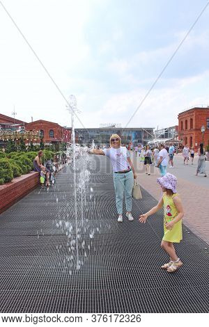 Lodz / Poland. 03 August 2019: Happy Mother With Little Daughter Fooling About Fountains. Cooling In