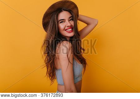 Graceful Tanned Woman In Stylish Brown Hat Standing In Confident Pose And Smiling. Studio Portrait O