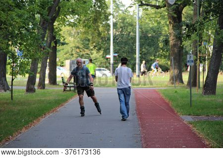 Lodz / Poland. 03 August 2019:  Beautiful City Park With Treadmill And Man Running On Roller Skates.