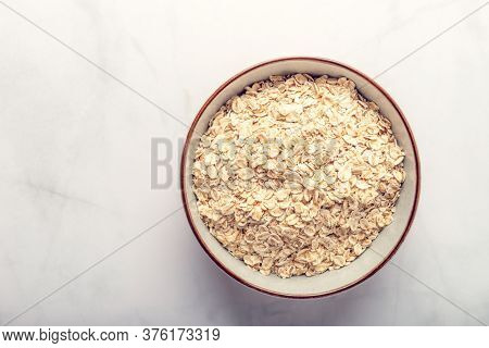 Gluten Free Rolled Wholegrain Oats Or Porridge Oats In Bowl, Marble Background, Space For Text