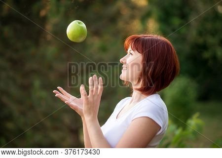Beautiful Woman With Red Hair Catching Big Green Apple Falling From Above Outdoors. Cheerful Woman T