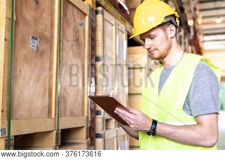 Portrait white caucasian warehouse worker use digital tablet working with inventory check in large warehouse distribution center. Reopening  Business warehouse technology and logistic concept