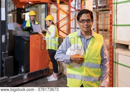 Portrait of Asian warehouse manager hold hard hat with warehouse worker operate forklift to check inventory in background. Reopening business warehouse technology and logistic concept.