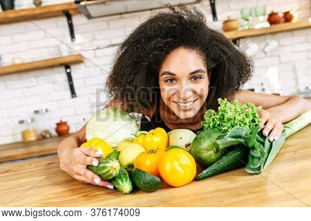 Attractive Young Multiethnic Woman With An Afro Hairstyle With Arms Wrapped Around Fresh Green Color