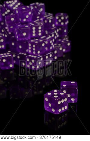 A Pile Of New Unused Casino Grade Dice Over A Black Reflective Surface.