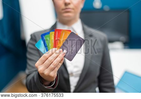 Unrecognizable Woman Dressed In A Suit Holds Multi-colored Plastic Credit Cards. A Faceless Bank Emp