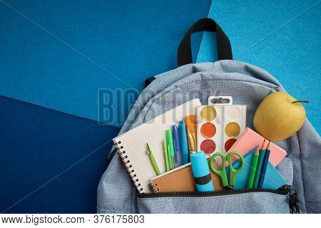 Stationery Set With Knapsack On Blue Background. School Supplies Top View For Advertising And Promot