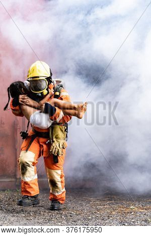 Firefighter rescue girl little child from burning building. He hold the girl and run out through smoke from building. Firefighter safety rescue from accident and public service concept.