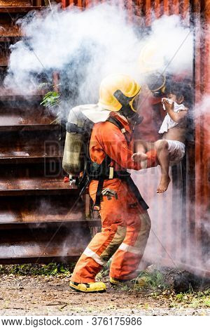 Firefighter rescue girl little child from burning building. He hold the girl and rescue her through window of building. Firefighter safety rescue from accident and public service concept.