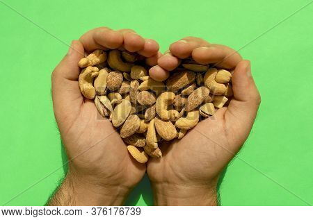 Mixed Nuts In Man's Hands Forming Heart Shape On Green Background. Top View. Salted And Spicy Pistac