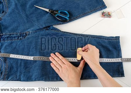 Caucasian Woman Hands Measure The Desired Length With A Measuring Tape On A White Table. Shorten The