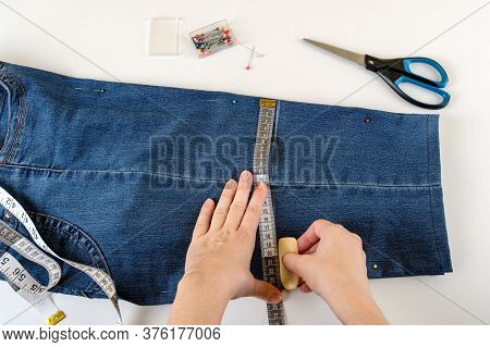 Caucasian Woman Hands Drawing A Cut Line On A Folded In Half Blue Denim Capris On A White Table. Sho