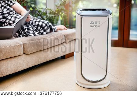 Air Purifier Cleans Up Air. Modern Air Purifier Cleans Up The Air In The Living Room With Woman Lyin