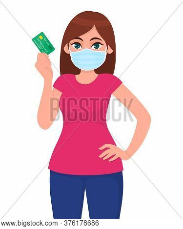 Young Girl In Medical Face Mask Showing Credit, Debit Card. Woman Holding Atm Transaction Card. Fema