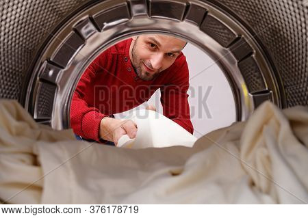 A Man Takes Clean Bed Linen Out Of The Drum Of The Washing Machine. A Concept To Illustrate A Bachel