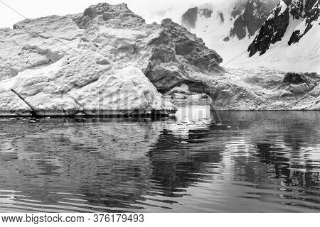 Black And White Floating Blue Iceberg Arch Reflection Paradise Bay Skintorp Cove Antarctica. Glacier