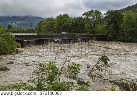 Wide Fast Stormy Mountain River Prut Flows Under The Bridge .  Natural Disasters In The Carpathians