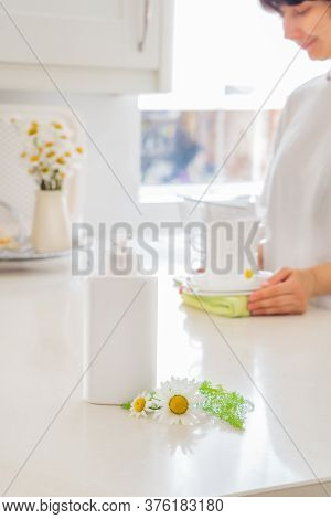 Eco Friendly Cleaning Dish Soap With Natural Chamomile Flower Ingredient And Woman Putting Clean Whi