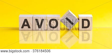 Wooden Blocks With The Text: Avoid. Yellow Background